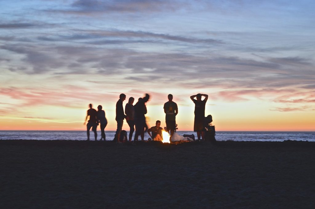 People enjoying outdoors campfire during sunset